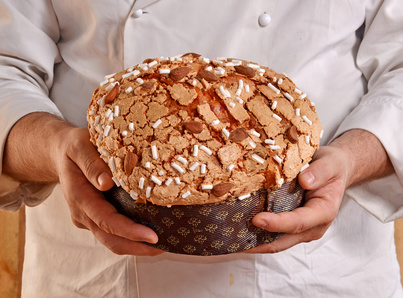 Manos de un panadero sujetando un panettone recien horneado.