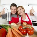 young beautiful couple working at home kitchen preparing vegetable salad together smiling happy